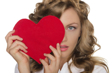 young woman holding heart in front of eye