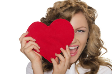 Smiling young woman holding heart in front of eye