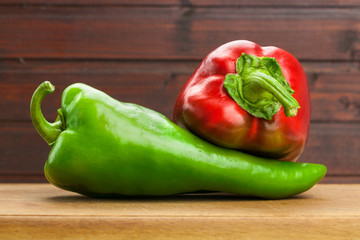 Red and green peppers on wooden board