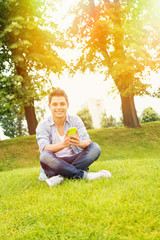 Young man with smart phone sitting in park