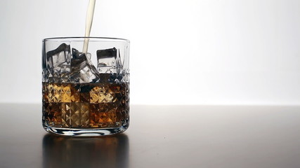 Whiskey pours into a glass with ice cubes (left)