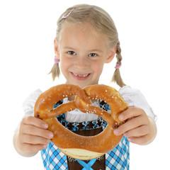 Kind in Dirndl zum Oktoberfest hält Brezel