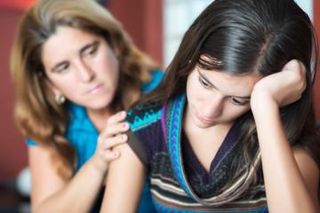 Mother comforts her teenage daughter