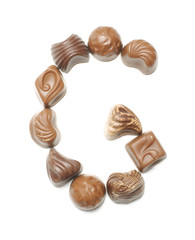 Alphabet letter G arranged from chocolate sweets isolated