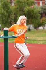 Senior woman exercising in outdoor fitness center