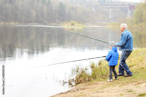 Grandfather and grandson are fishing - 68808340