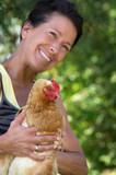 Frau mit Huhn in den Händen