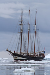 Black tourist sailing ship in Antarctic waters clogged with ice