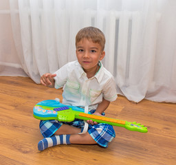 child with a guitar at home