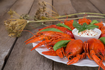 Plate with red boiled crayfish with sauce on the side