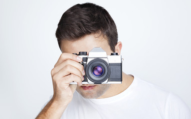 Close-up of a young man using a retro camera against gray backgr