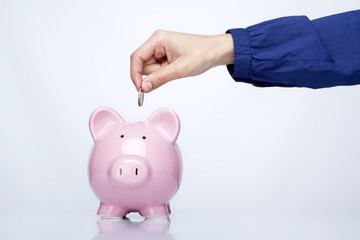 Female hand putting coin into a piggy bank over gray background