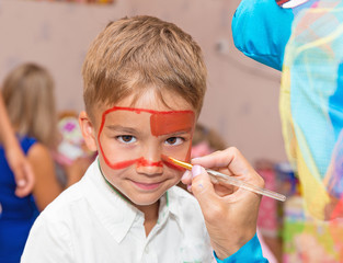 applying a mask of paint on the face of a child