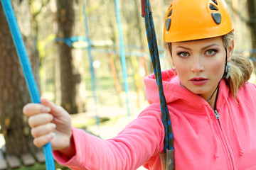 girl in the outfit climbing climbs over obstacles between trees