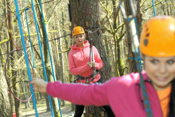 Two  girls in a special outfit climbing among the trees