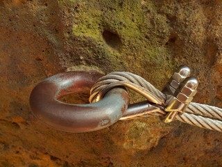 Detail of rope end anchored into sandstone rock. Iron twisted r