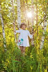 Little girl among birches