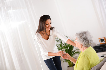 cheerful young girl taking care of elderly woman at home