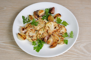 Warm appetizer of fried pieces of cauliflower with garlic and on