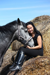 Beautiful woman sitting on hay bale and gray horse