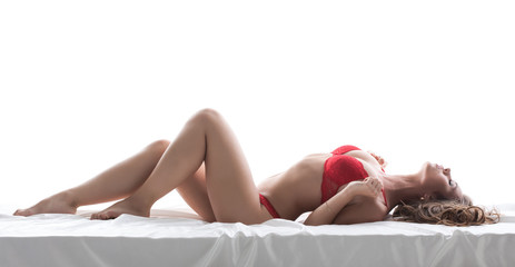 Excited slim model posing lying in red lingerie