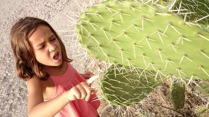 Niña pinchándose con cactus