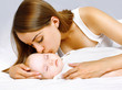 Happy mother and sleeping baby in the bed
