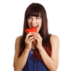 junge Frau beißt in ein rotes Herz