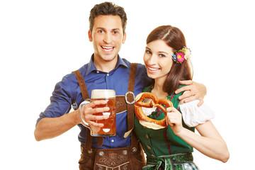 Mann und Frau beim Oktoberfest mit Bier und Brezel