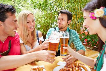 Freunde stoßen mit Bier an im Biergarten