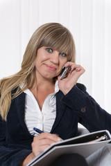Frau telefoniert und macht Notizen