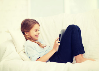 smiling girl with tablet computer at home
