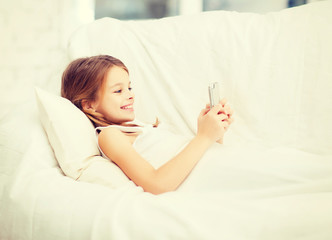 little girl with smartphone playing in bed