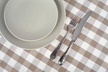 Grey plate with fork and knife on beige checkered tablecloth.