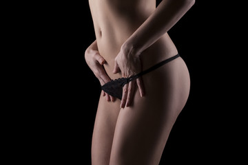 woman taking off her black panties on a dark background