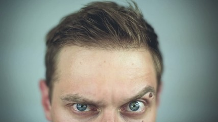 Close-up of a green big eyed man raising eyebrow