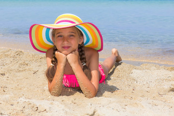 Girl with colorful hat on the beach