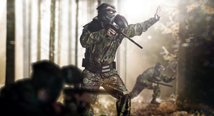 Paintball team in action forest location