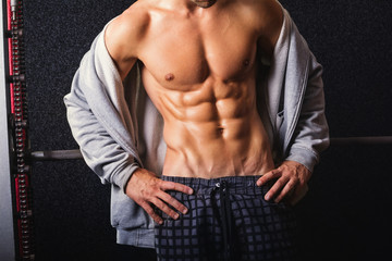 Young bodybuilder man with abs in gym