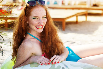 Smiling girl with freckles on the beach
