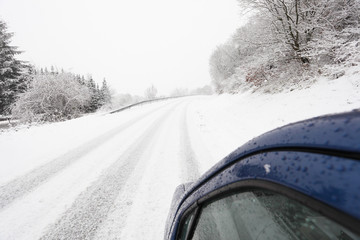Car on a snowy country road in winter