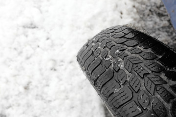 Closeup of snow tire on a snow-covered road