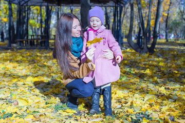 Portrait of cute girl and happy mother in yellow autumn park