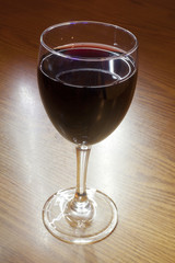 A glass of Red Wine on a wooden table.
