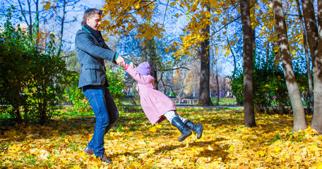 Adorable little girl and happy father having fun in autumn park