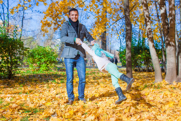 Adorable little girl with happy dad having fun in autumn park on