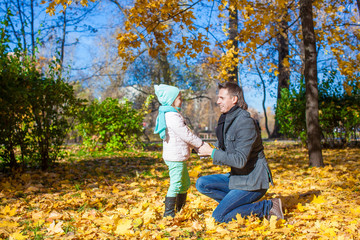Happy father with his cute daughter in autumn park outdoor