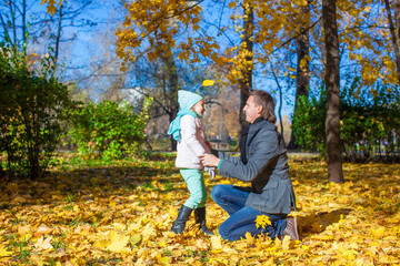Happy father with his cute daughter in autumn park