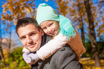 Portrait of happy father with his cute daughter in autumn park