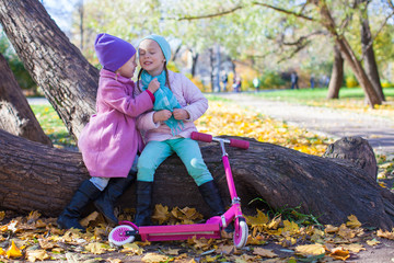 Little beautiful girls with scooter in the autumn park
